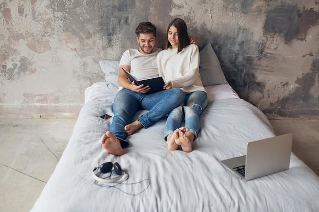 Jovem casal feliz e sorridente, sentado na cama em casa, com roupa casual, lendo um livro de jeans, um homem e uma mulher passando um tempo romântico juntos