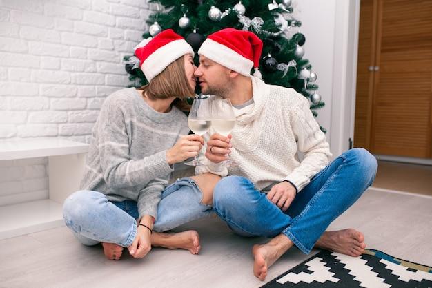 Jovem casal feliz em chapéus de natal, perto de uma árvore de natal beijando, segurando copos de vinho. celebração de ano novo