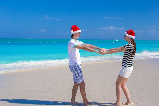 Jovem casal feliz em chapéus vermelhos de papai noel na praia branca