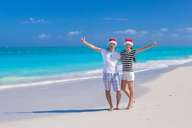 Jovem casal feliz em chapéus vermelhos de papai noel na praia tropical