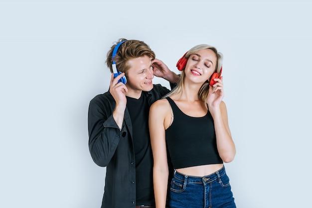 Jovem casal feliz em fones de ouvido escutando música