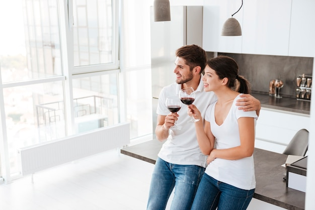 Jovem casal feliz em pé e bebendo vinho tinto na cozinha