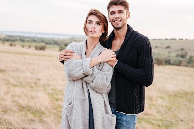Jovem casal feliz em pé e se abraçando no campo de grama no outono