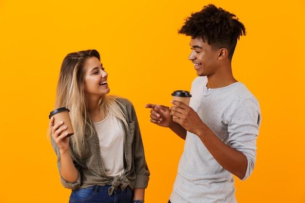 Jovem casal feliz em pé, isolado sobre uma parede amarela, bebendo café