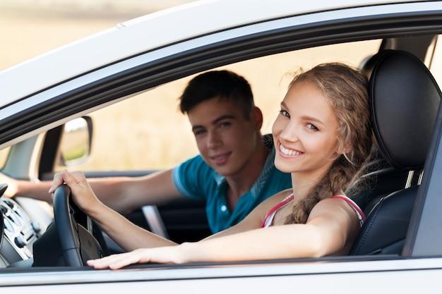 Jovem casal feliz em um carro sorrindo - conceito de comprar um carro.