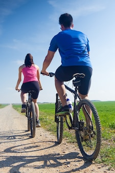 Jovem casal feliz em um passeio de bicicleta no campo