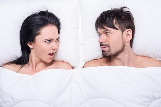 Jovem casal feliz em uma cama está olhando para o outro.