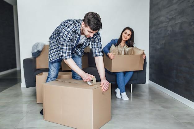 Jovem casal feliz embalando caixas de papelão durante a mudança
