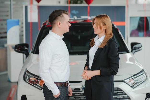Jovem casal feliz escolhe e comprando um carro novo para a família na concessionária.