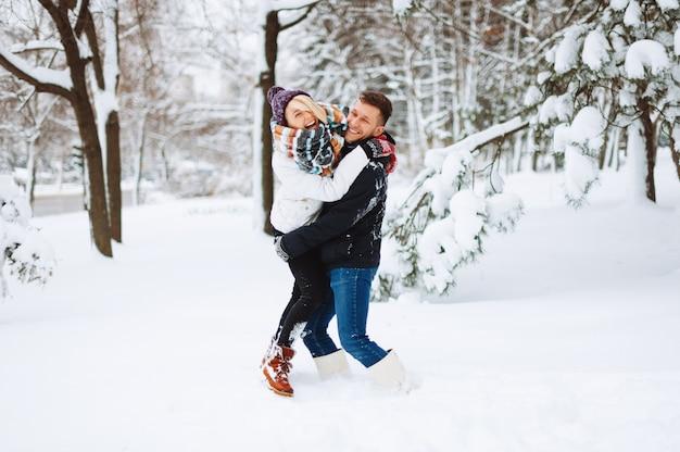 Jovem casal feliz está brincando na neve e aproveitando seu tempo juntos no parque no inverno.