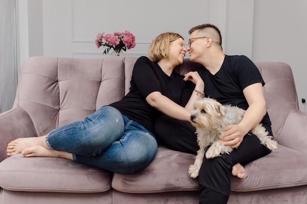 Jovem casal feliz está se divertindo no sofá-de-rosa em seu cachorro yorkshire terrier de sala de estar.