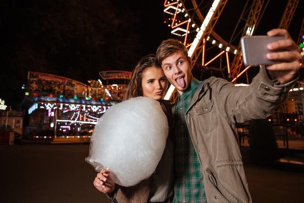 Jovem casal feliz fazendo caretas e tirando selfie no parque de diversões