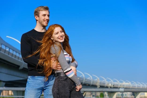 Jovem casal feliz fica contra a parede de um céu azul e uma ponte com roupas casuais e sorri