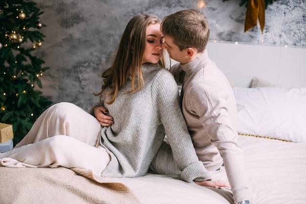 Jovem casal feliz ficando na cama em casa