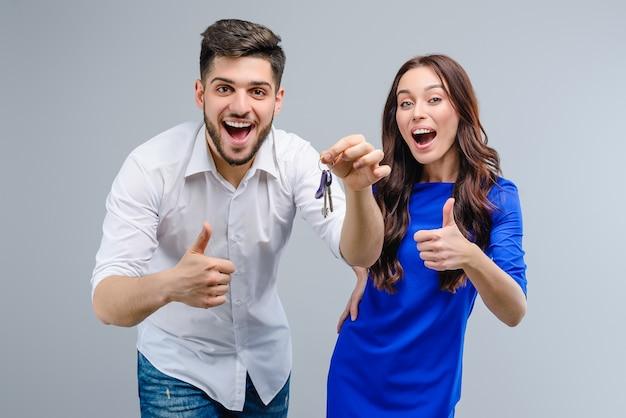 Jovem casal feliz homem e mulher com chaves isoladas