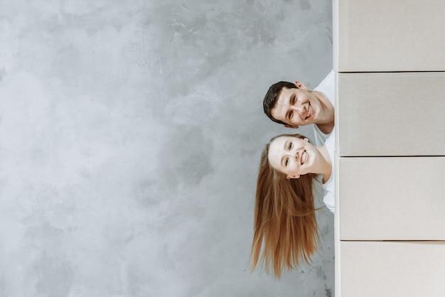 Jovem casal feliz homem e mulher olhando por trás do espaço de cópia excelente de caixas.