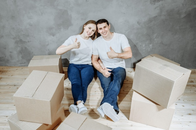 Jovem casal feliz, homem e mulher, sentados no chão entre as caixas corton para se mudarem para sua nova casa