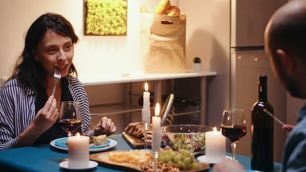 Jovem casal feliz jantando festivo, comendo, bebendo, conversando, rindo, sorrindo, relaxando na mesa da cozinha. amantes passando momentos românticos durante deliciosas refeições à luz de velas