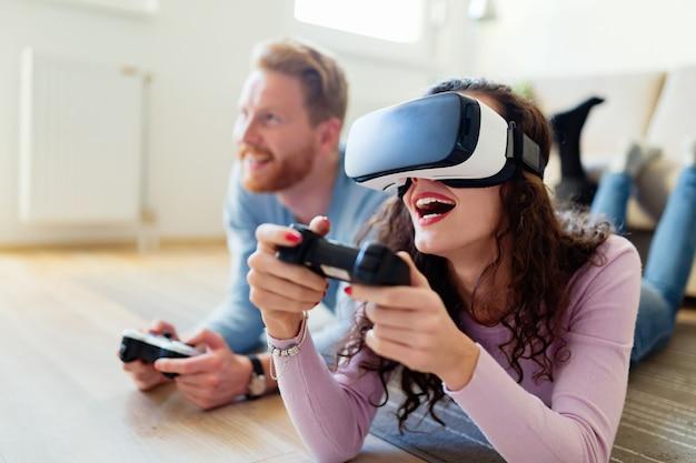 Jovem casal feliz jogando videogame com fones de ouvido de realidade virtual em casa