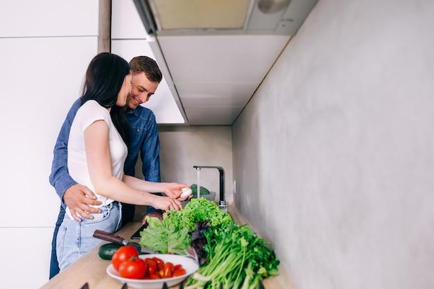 Jovem casal feliz lavando legumes na cozinha enquanto prepara os ingredientes para o jantar