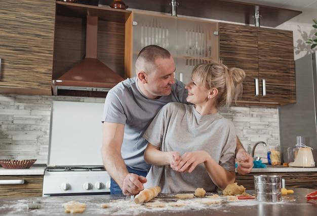 Jovem casal feliz marido e mulher juntos, se divertindo fazendo biscoitos em casa na cozinha. alegria e compreensão mútua na família.