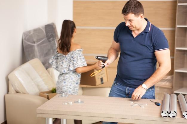 Jovem casal feliz montando móveis de auto-montagem enquanto se mudavam