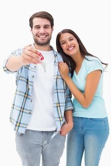 Jovem casal feliz mostrando nova casa chave