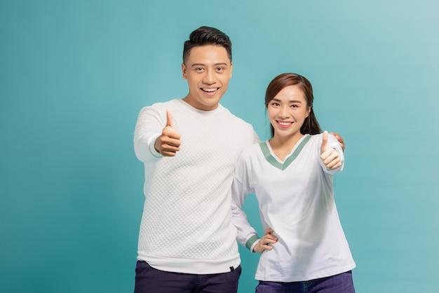 Jovem casal feliz mostrando os polegares para cima e olhando para a câmera isolada sobre o azul