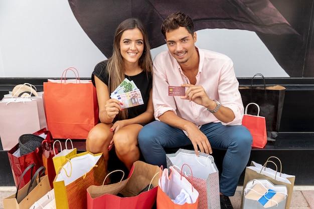 Jovem casal feliz mostrando poupar dinheiro para compras extras