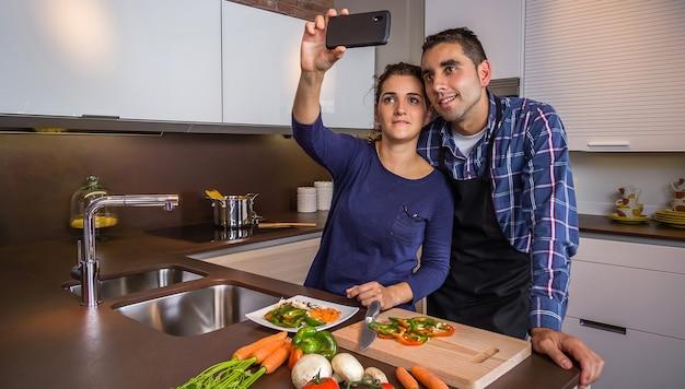 Jovem casal feliz na cozinha de uma casa tirando uma selfie com um smarphone enquanto prepara uma comida saudável