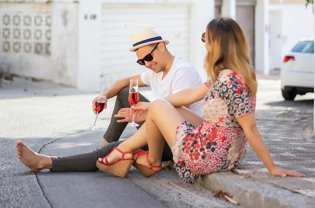 Jovem casal feliz no amor caminha pelas pequenas ruas em espanha, beber champanhe, rir. vacatio