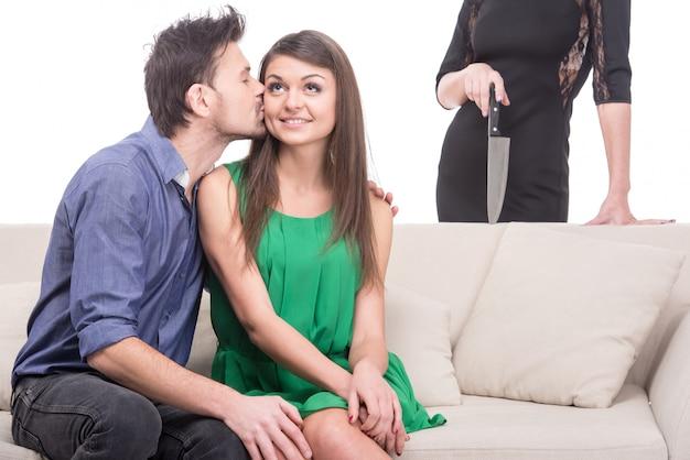 Jovem casal feliz no sofá em primeiro plano