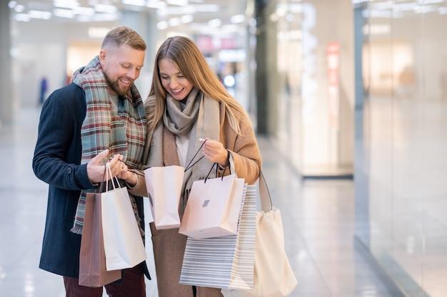 Jovem casal feliz olhando para comprar em uma das sacolas de papel depois de fazer compras no centro comercial contemporâneo