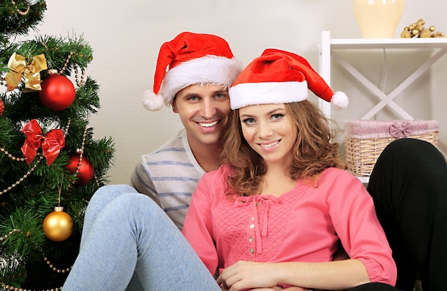 Jovem casal feliz perto da árvore de natal em casa