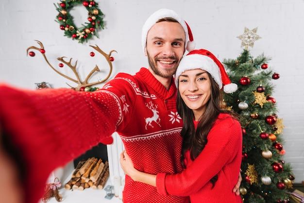 Jovem casal feliz perto de árvore de natal