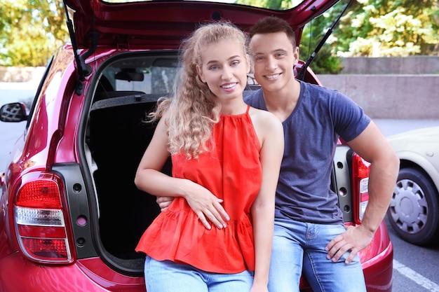 Jovem casal feliz perto do carro ao ar livre