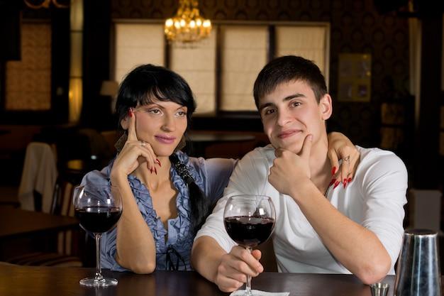 Jovem casal feliz posando feliz sentado no bar bebendo vinho tinto em um local chique
