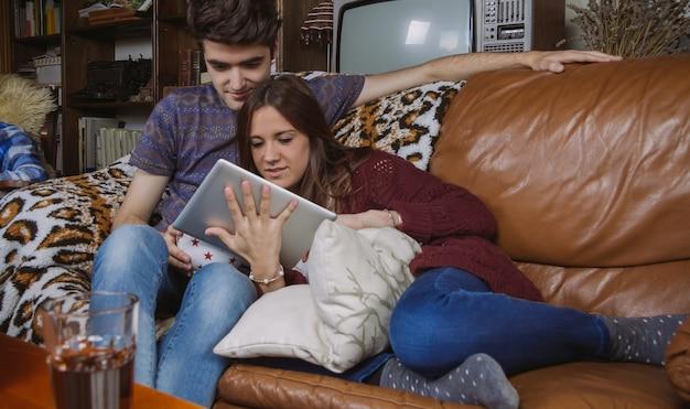 Jovem casal feliz procurando tablet digital sentado em um sofá em casa