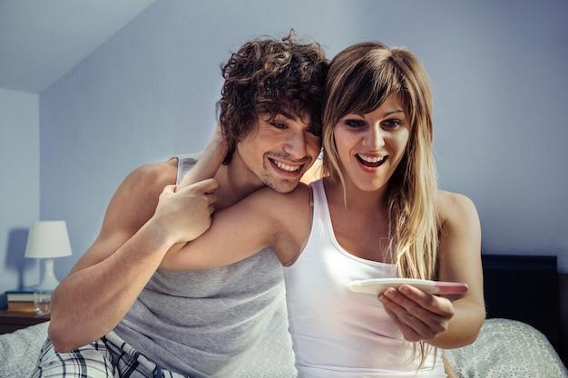 Jovem casal feliz procurando um teste de gravidez sentado na cama