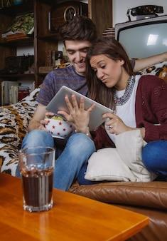 Jovem casal feliz rindo enquanto olha o tablet digital sentado em um sofá em casa
