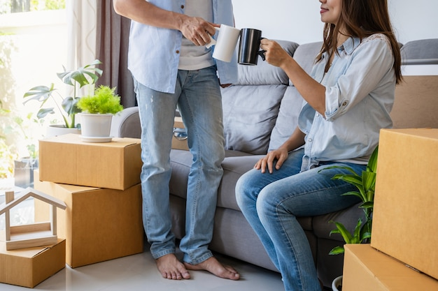 Jovem casal feliz se mudando para a nova casa, sentado e relaxando no sofá