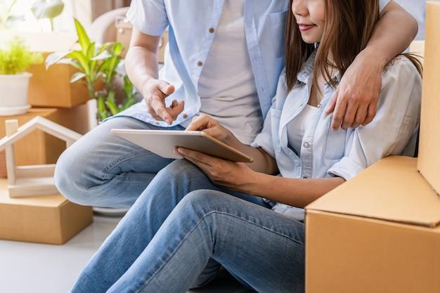 Jovem casal feliz se mudando para uma casa nova, sentado e relaxando no chão e procurando ideias de decoração para casa no tablet