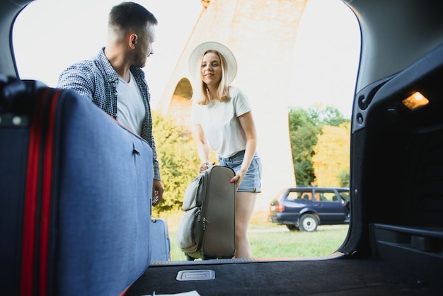 Jovem casal feliz se preparando para ir de férias de férias. coloque as malas no porta-malas do carro
