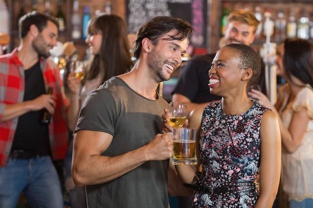 Jovem casal feliz segurando canecas de cerveja