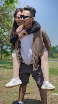Jovem casal feliz segurando seu parceiro no parque na primavera