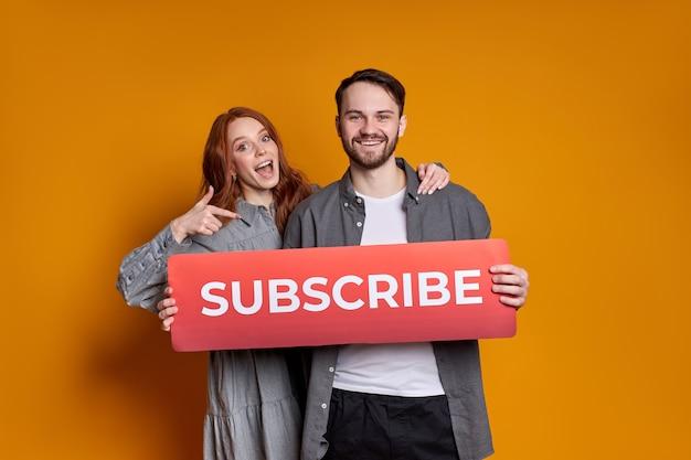 Jovem casal feliz segurando um papelão com inscrição, sorrindo para a câmera, quer mais curtidas e assinantes