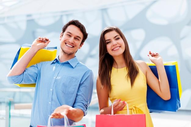 Jovem casal feliz segurando uma sacola de compras