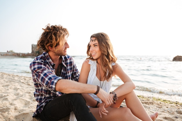 Jovem casal feliz sentado e conversando na praia