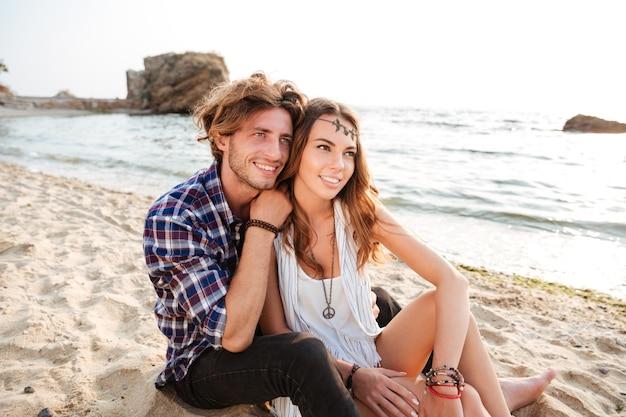 Jovem casal feliz sentado e se abraçando na praia