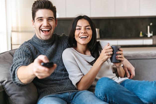 Jovem casal feliz sentado em um sofá em casa, assistindo tv